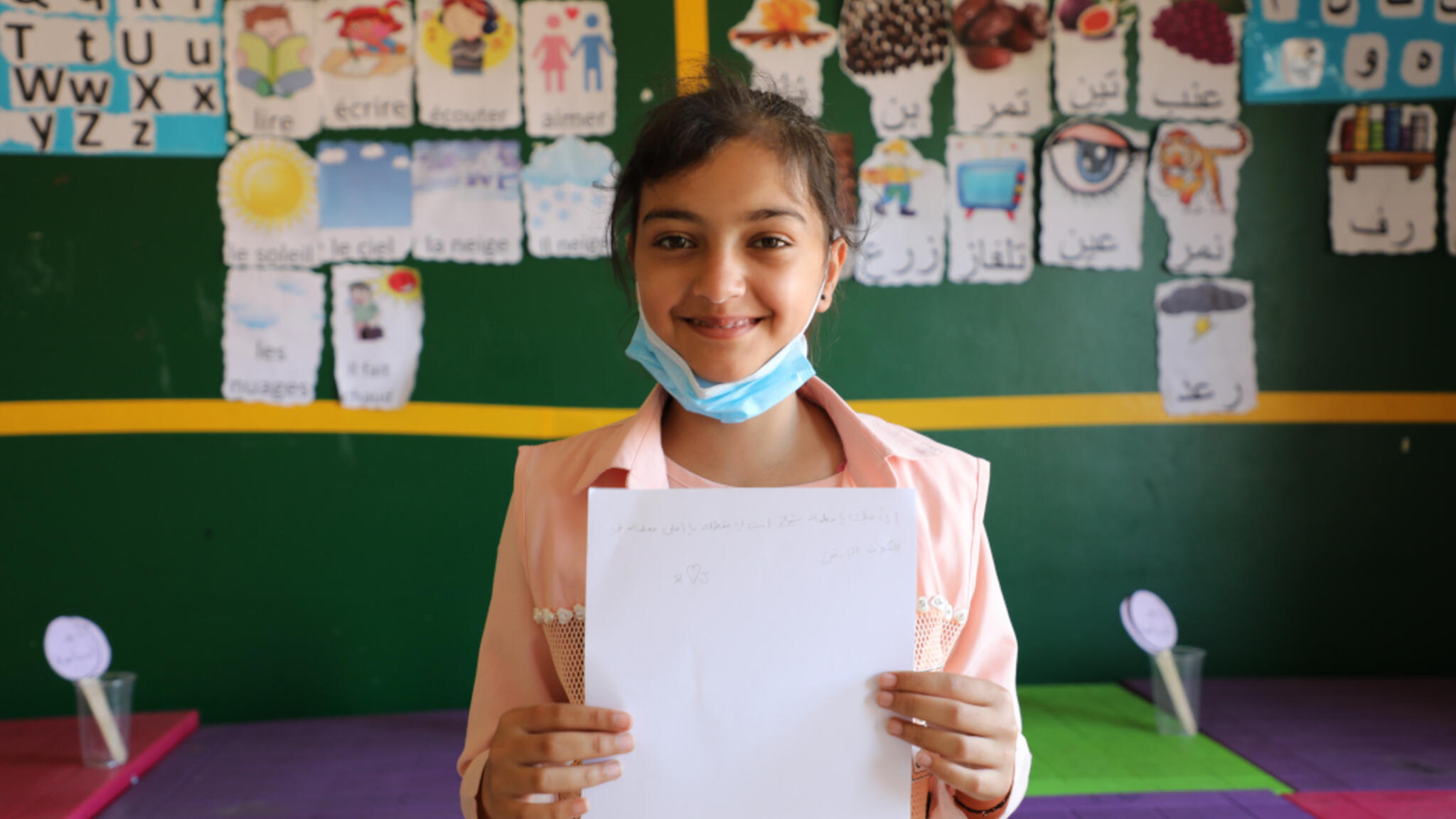 Joumana holding her schoolwork towards the camera
